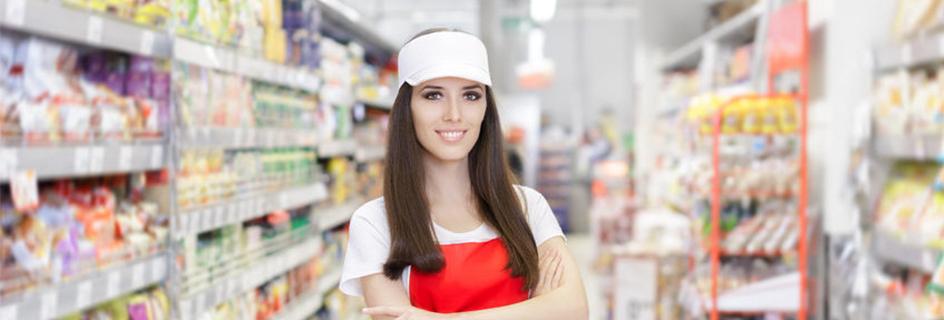 Une employée libre service qui pose devant son rayon