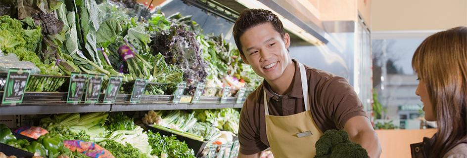Un vendeur au rayon fruits et légumes qui conseille une cliente